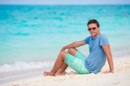 Young beautiful man listening to music on white beach Stock Photo