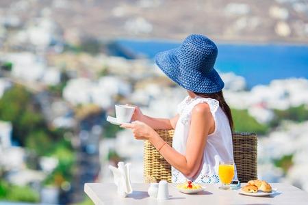 paisaje mediterraneo: Mujer de desayunar en el café al aire libre con vista magnífica de la ciudad de Mykonos. Foto de archivo