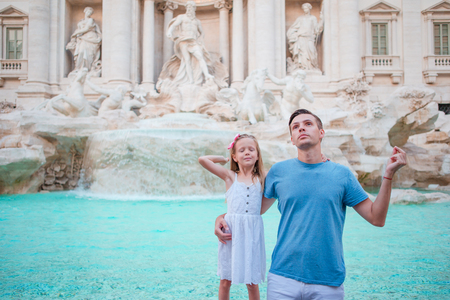 Young man and little girl near fountain Fontana di Trevi with coins in hands