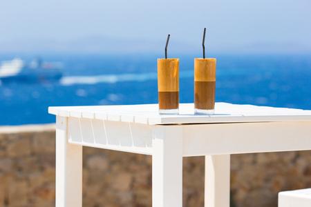 海の背景の木のテーブルの上のコーヒーのカフェラテ