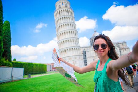 Young happy girl with toristic map on travel to Pisa. Tourist traveling visiting The Leaning Tower of Pisa, Italy Stock Photo