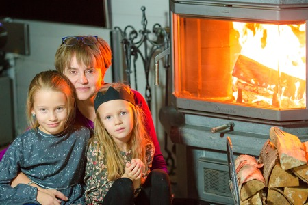 fireplace family: Family sitting by a fireplace in their family home on Christmas eve Stock Photo