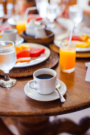 Black coffee, juice and fruits for breakfast at a cafe in the resort