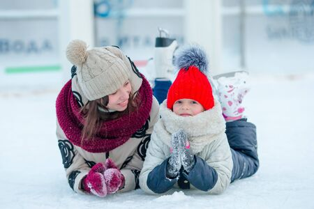 Smiling young mother and her cute little daughter ice skating together Stock Photo