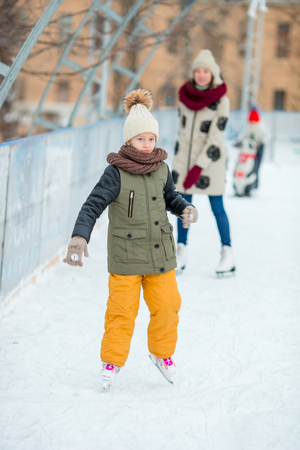 Adorable little girl skating on the ice-rink Stock Photo