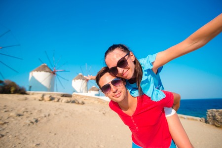 copule: Family taking selfie with a stick in front of windmills at popular tourist area on Mykonos island, Greece Stock Photo