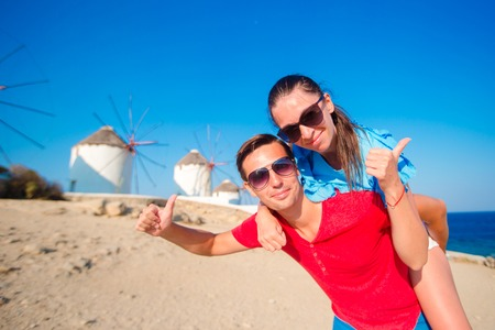 copule: Family in front of windmills at popular tourist area on Mykonos island, Greece