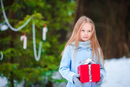 Adorable little girl with Christmas box gift on Xmas eve outdoors