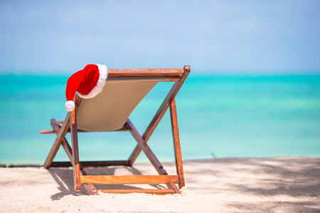 beachfront: Christmas on the beach - chair with Santa hats at sea. Christmas vacation concept