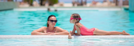 Family enjoying summer vacation in luxury swimming pool Stock Photo