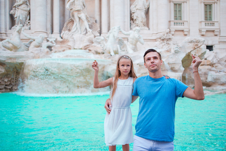 Happy family trowing coins at Trevi Fountain, Rome, for good luck. Little girl and father making a wish to come back.