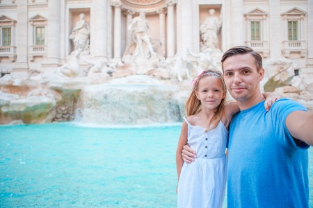Young father and little girl making selfie background Trevi Fountain, Rome. Family portrait at famous places in Europe Stock Photo