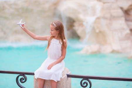 Adorable little girl with toy airplane background Trevi Fountain, Rome, Italy.