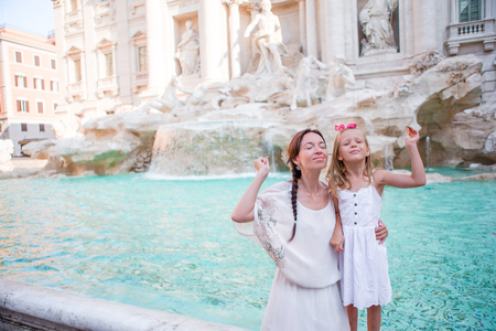 Mom and kid trowing coin at Trevi Fountain for good luck. Little girl making a wish to come back to Rome