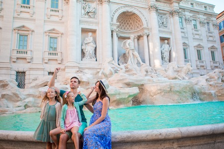 Happy family trowing coins at Trevi Fountain, Rome, for good luck. Little girls and parents making a wish to come back.