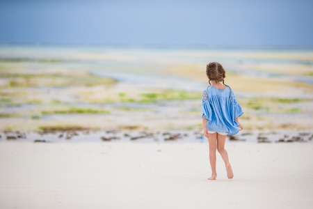 Adorable little girl on beach vacation during low tide