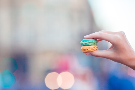 versicolor: Girl holding colorful French macarons in hands background lively street Stock Photo