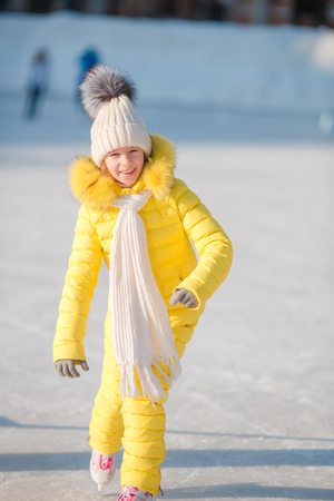 Adorable little girl going skate in winter snow day outdoors Stock Photo