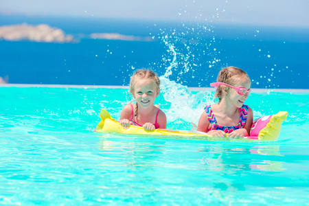 Adorable little girls playing in outdoor swimming pool with beautiful view Stock Photo