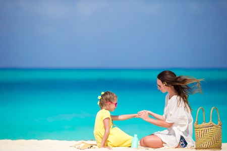Ypung mother applying sun cream to daughter hands