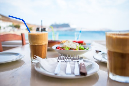 Traditional lunch with delicious fresh greek salad, frappe and brusketa served for lunch at outdoor cafe
