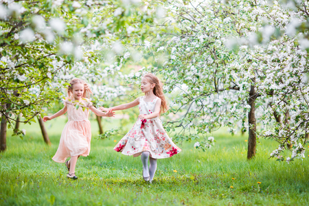 Beautiful girls in blooming apple tree garden enjoy warm spring day Stock Photo