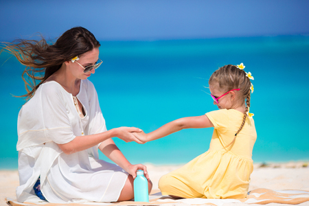 Young mother applying sun cream to daughter hands in hot beach day