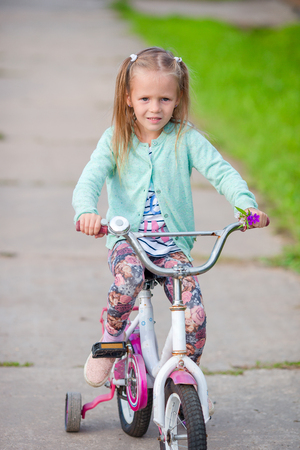 back alley: Adorable girl riding a bike at beautiful summer day outdoors