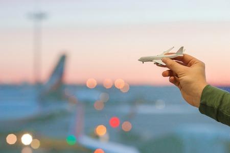 空港の背景の大きな窓で、飛行機モデルのグッズを持っているクローズ アップ手 写真素材