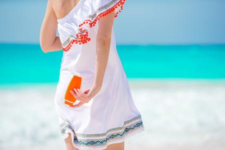 Closeup suncream bottle in female hands on the beach