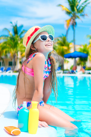 suncare: Little girl with bottle of sun cream sitting on the edge of swimming pool