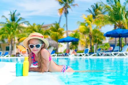 suncare: Little girl with bottle of sun cream in swimming pool Stock Photo