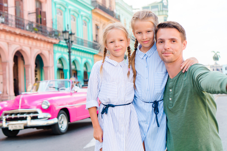 capitolio: Family in popular area in Old Havana, Cuba. Portrait of two kids and young dad outdoors on a street of Havana Stock Photo