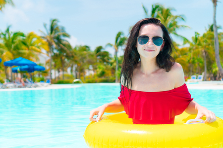 resort life: Beautiful young woman relaxing in swimming pool. Back view of girl in outdoor pool at luxury hotel