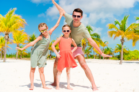 yahoo: Father and little girls have a lot of fun on white sandy beach
