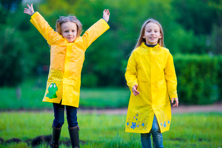 Adorable little girls wearing waterproof coat have fun outdoors