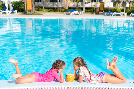 Little girls in outdoor swimming pool drink coconut milk Stock Photo