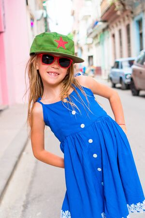 Adorable little girl in popular area in Old Havana, Cuba. Portrait of kid in old street of the city Stock Photo