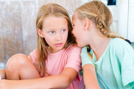 Funny little girls in an outdoor cafe on sunny summer day. Kids whisper while waiting the food Stock Photo