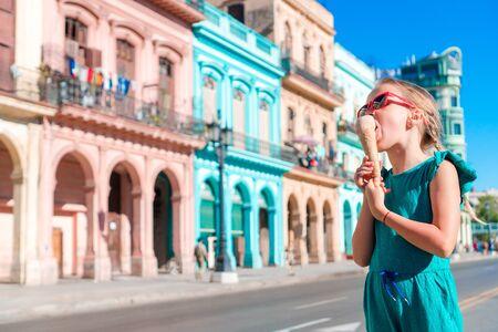 capitolio: Adorable little girl eating ice-cream in popular area in Old Havana, Cuba. Portrait of cutiest kid outdoors on a street of Havana Stock Photo