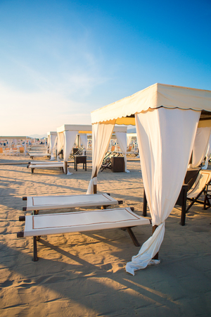forte: Wooden sunbeds in front of a turquoise sea in the evening light. Sunbeds in famous italian sand beach at Forte dei Marmi
