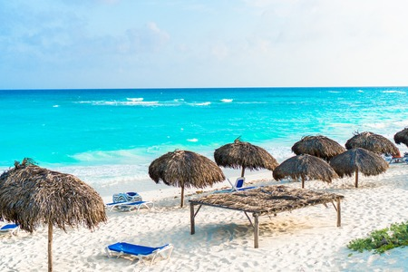 Beach sunbeds and umbrellas on white beach in caribbean island