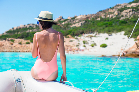 resort life: Beautiful young woman relaxing on the boat in amazing turquoise lagoon on Sardinia