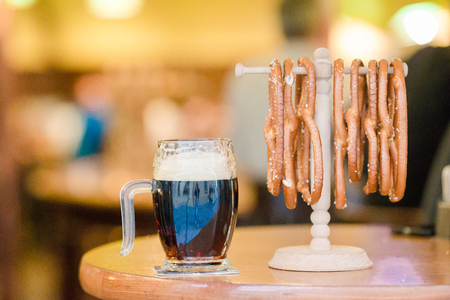 Close up salted tasty pretzels and beer on wooden background. Stock Photo