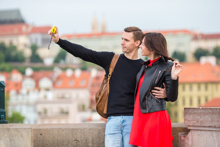 most popular: Young couple traveling on holidays in Europe smiling happy. Caucasian family making selfie in popular Karlov Most