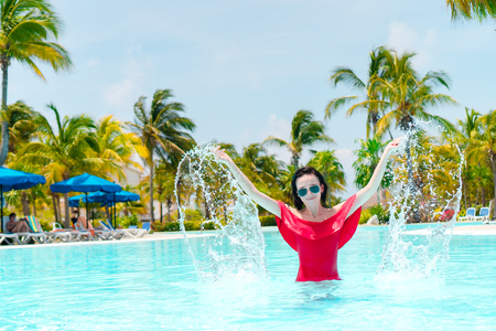 Beautiful young woman relaxing in swimming pool. Happy girl in outdoor pool at luxury hotel Stock Photo