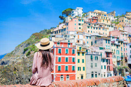 Young woman with great view at old village Riomaggiore, Cinque Terre, Liguria, Italy. European italian vacation.