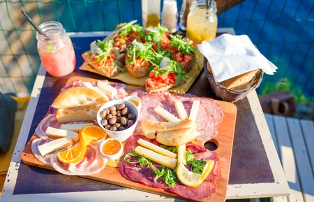 mediterranean culture: Tasty italian food. Fresh bruschettes, cheeses and meat on the board in outdoor cafe with amazing view in Manarola, Italy
