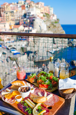 Tasty italian snacks. Fresh bruschettes, cheeses and meat on the board in outdoor cafe with amazing view in Manarola, Italy Stock Photo