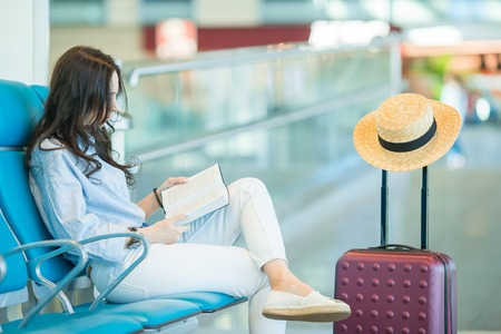 Young woman in an airport lounge reading book while waiting for flight aircraft. Archivio Fotografico